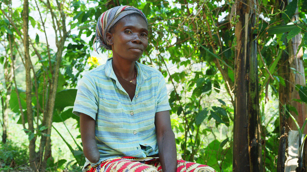 Cifa, a 38 year old coffee producer and ERW survivor, has a below elbow amputation on her right arm. She is married with three children who all work the farm because she does not have enough money to pay for their education.