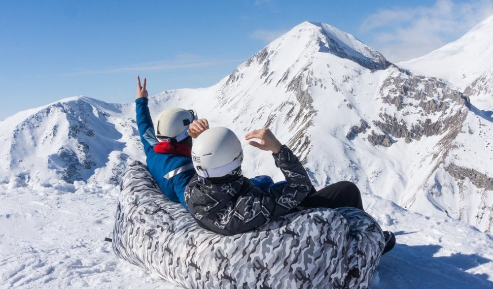 Two people sat on top of a mountain sitting on a Chillax seat