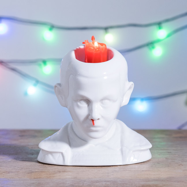 White model of Eleven with a red candle inside and red candle wax dripping from the nose
