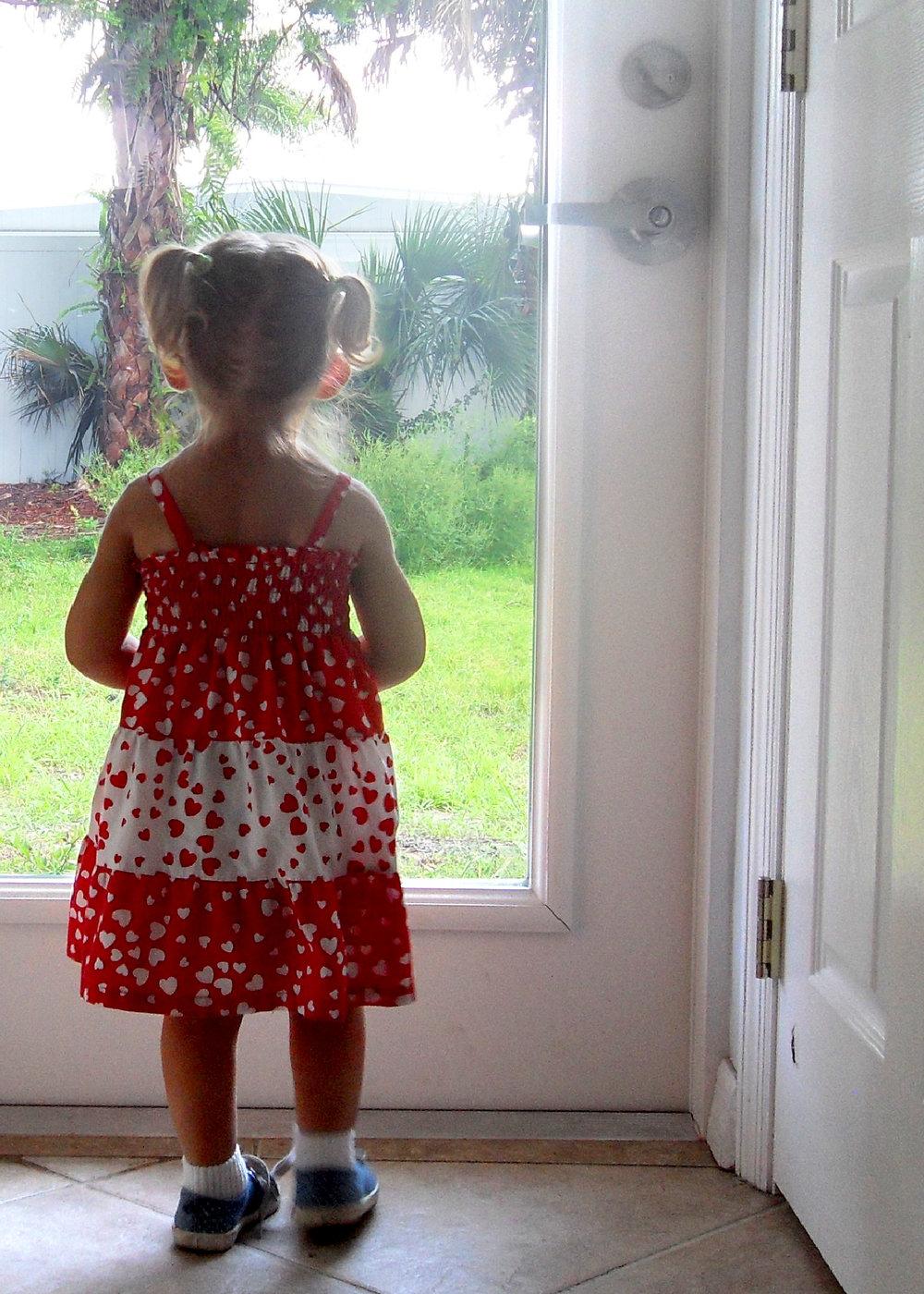 little-girl-looking-out-door.jpg