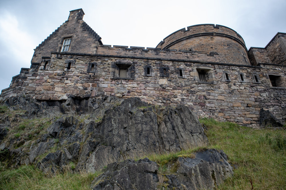 The grand, rocky castle fortress of Edinburgh Castle in Scotland. Learn my money hacks and travel tips for saving money on your Sctoalnd honeymoon! | MissFunctional Money