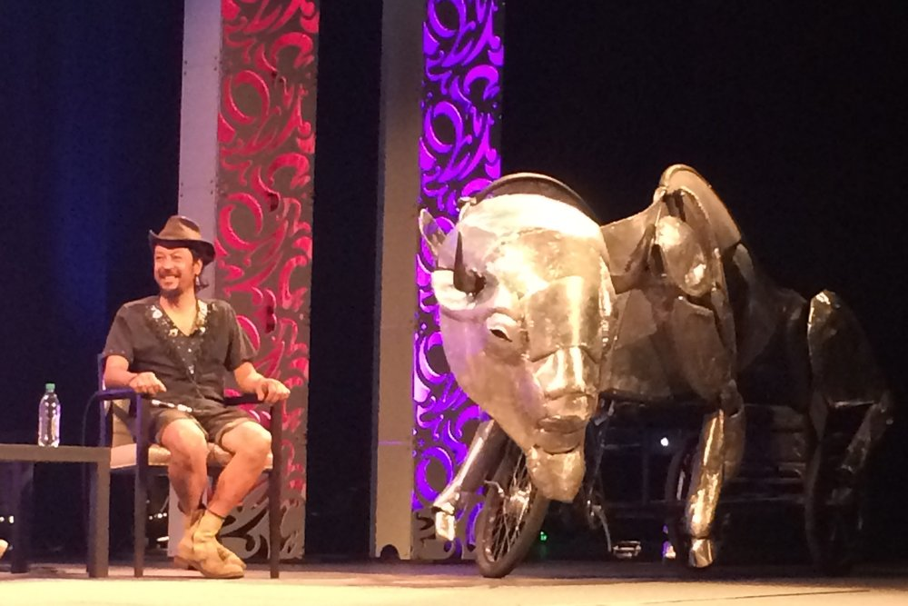 Symposium of the Americas - Artist Juan Martinez rode the pedal-powered bison  onstage at the Biennial of the Americas.