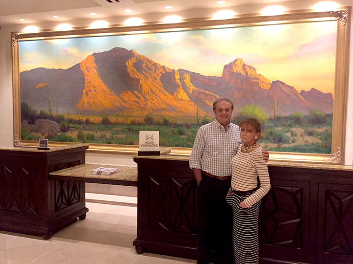 "KARL AND HIS WIFE, RENEE BAGLEY THOMAS, AT THE HYATT HOTEL IN SCOTTSDALE, AZ.. BEHIND THEM IS KARL'S 60"" X 200"" PAINTING ""CAMEL BACK MOUNTAIN"""