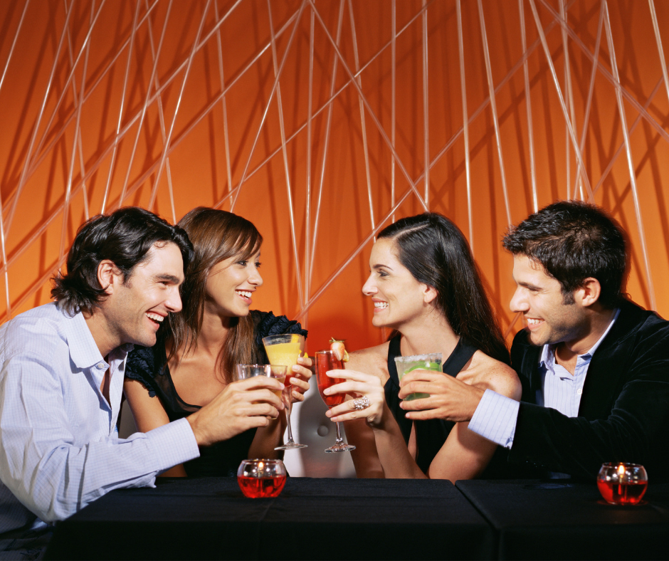 four friends socialising with drinks in a bar. showing how to be socially confident