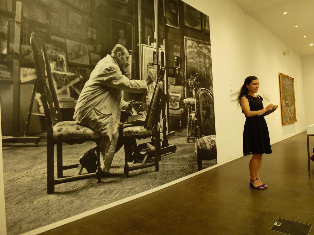 Pamela Corvalan, commissaire de l'exposition, devant une très belle photo de Louis de Meuron dans son atelier. Cet espace est propice au peintre pour élaborer et affiner son style, créant un univers paradisiaque issu des impressions, paysages ou personnes l'entourant.