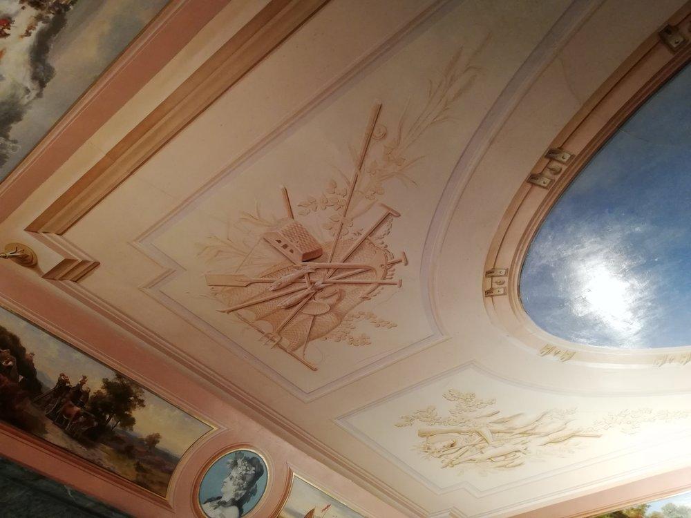 Le plafond, signé par le peintre-décorateur Valentino, s'orne d'un immense hublot ouvert sur un ciel bleu. Les 4 angles présentent des motifs symbolisant la chasse, la vendange, la moisson et la pêche.