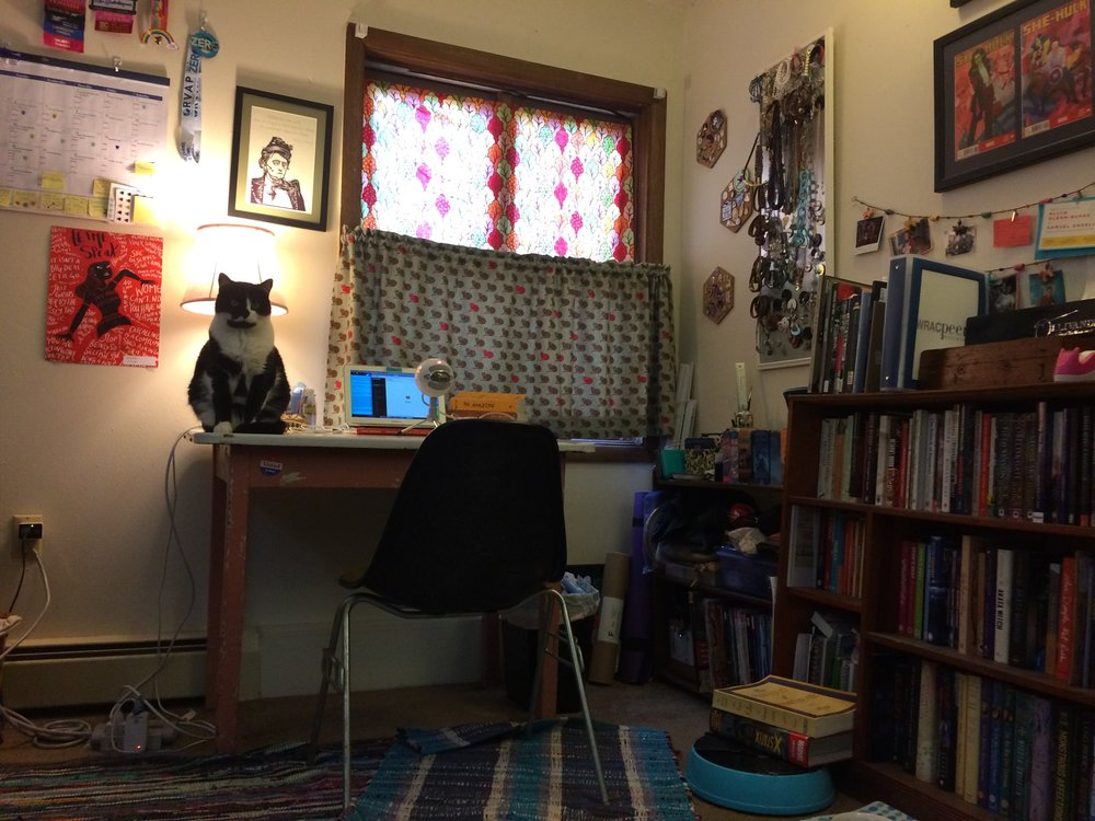 My studio, minus the artist. Featuring Fiona in her typical spot. I curate this space over the past three years to be cozy, comfortable, and full of feminist art, writing, and inspiration. The curtains were made by my mother, an artist in her own right. While the cheerful curtains serve the purpose of helping with sound quality they were originally created due to Borbie destroying the blinds like a true cat.