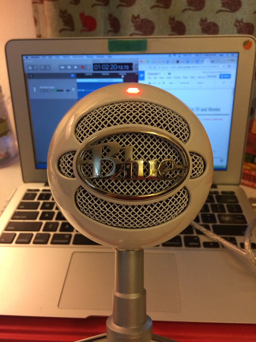 My view while recording. My beautiful Snowball mic. The Snowball and the Yeti are the two mics I most heard recommended from other pocasters, and as the snowball is less expensive (though still a hit to the pocketbook, yeah, I still carry a pocketbook. What of it?) it's the one I went with. Out of focus on the laptop screen are the two things I need to record,my script and Garageband (Garageband is considered an inferior software by most podcasters, but I don't have room for anything else on my laptop).