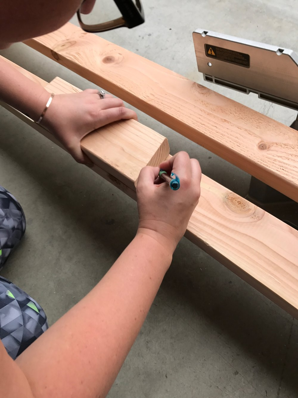 - We then cut a scrap piece at an angle to ensure that the rungs would be level with the floor once it was completed. I made a line at each of the measurements we marked earlier using our scrap piece as a guide. We did this so we knew where the rungs needed to be lined up. I did this on both 7ft pieces.