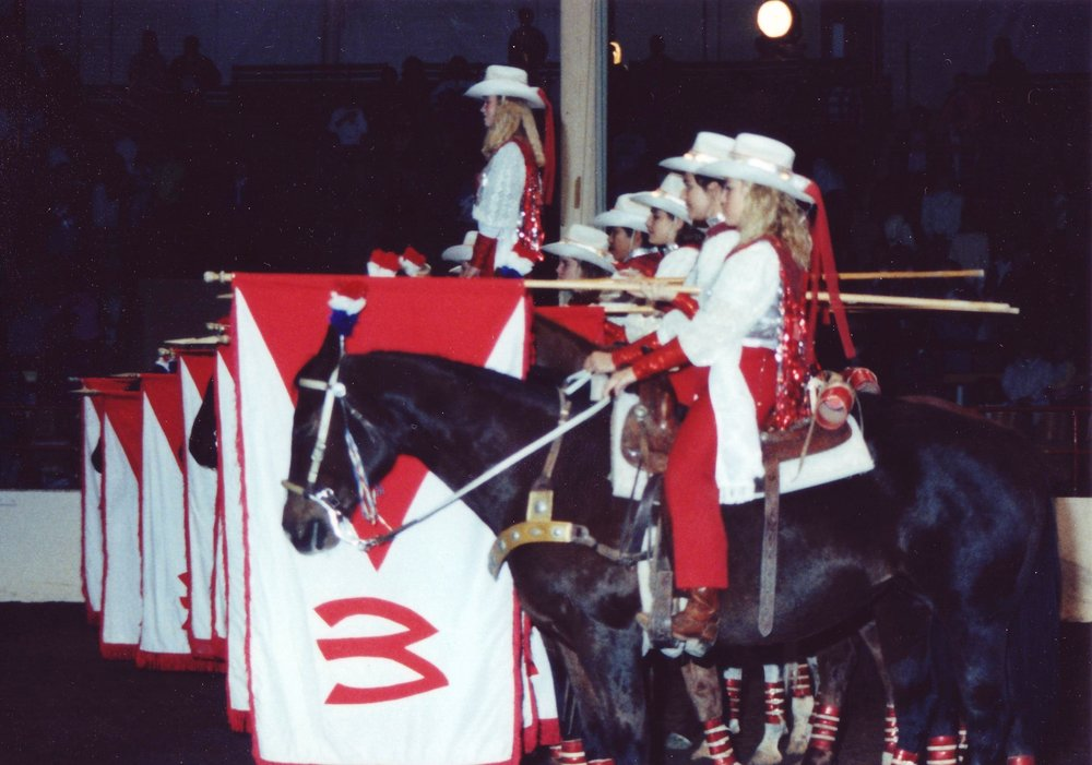 The Varsity Red Team Grand Entry team salutes the American Flag during the National Anthem at Annual Show, 1991