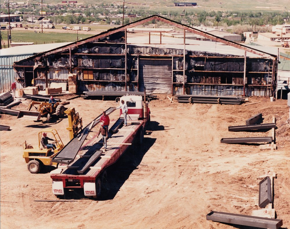 Volunteers deconstruct what remained of the damaged steel girders in the Red Arena.  The old Red Arena's north-facing wall was the only thing remaining in this picture -- taken during Spring / Summer of 1986.  Volunteers organized and removed the old steel, while the new steel structural beams were unloaded after transporting them from Independence, Missouri.  In this picture: Woody Ellis is on the tractor (blue jacket), while Bruce Slaugh drives on the forklift (plaid shirt).  Stu Rydgren (white jacket), Ron Kronauge (red jacket), and Glen Rowell (brown jacket) are on the flatbed.