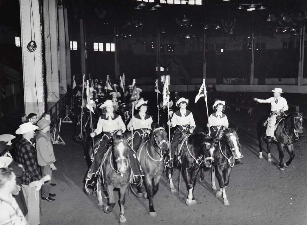 Westernaires Founder and Director, Elmer Wyland (right), directs the troops through warm-up maneuvers in the Stockyard Stadium prior to their performance in the 1952 National Western Stock Show.