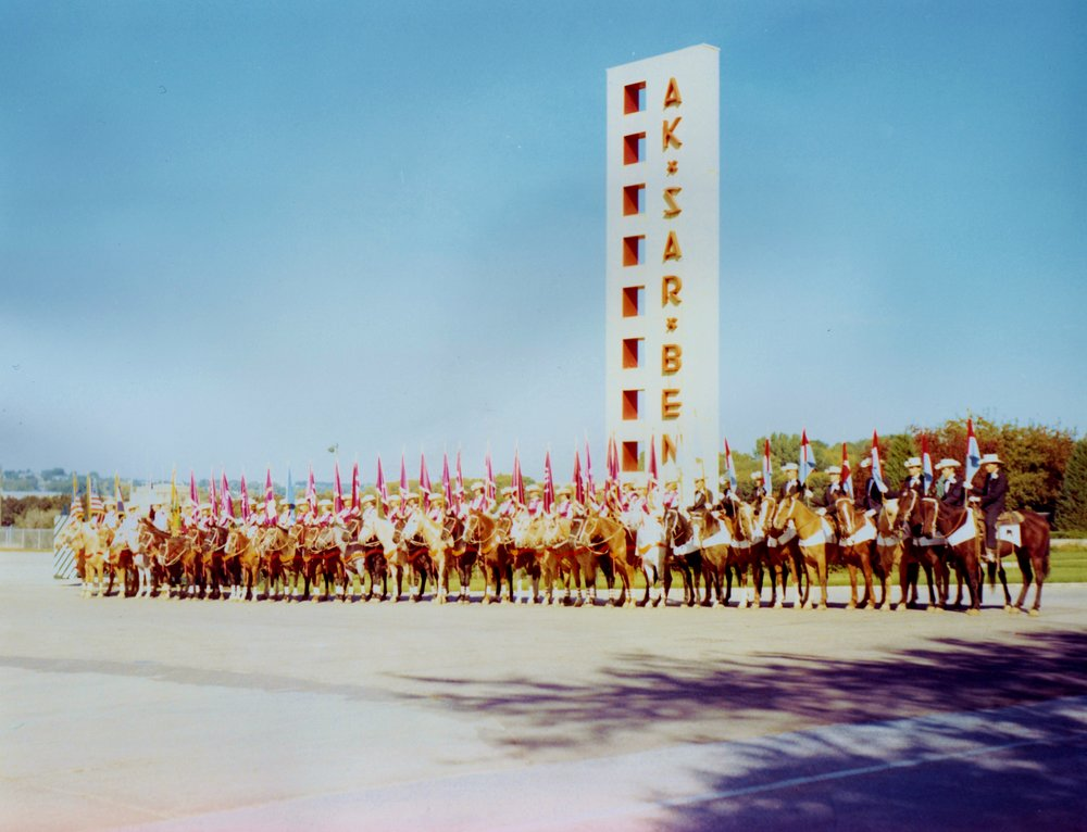 The Varsity Big Red Team lines up in front of the famous Ak-Sar-Ben (Nebraska spelled backward) monument during their performances at the 1965  AkSarBen Stock Show  and Rodeo.  Though the event has changed and evolved over the years and has a  rich history in Nebraska .