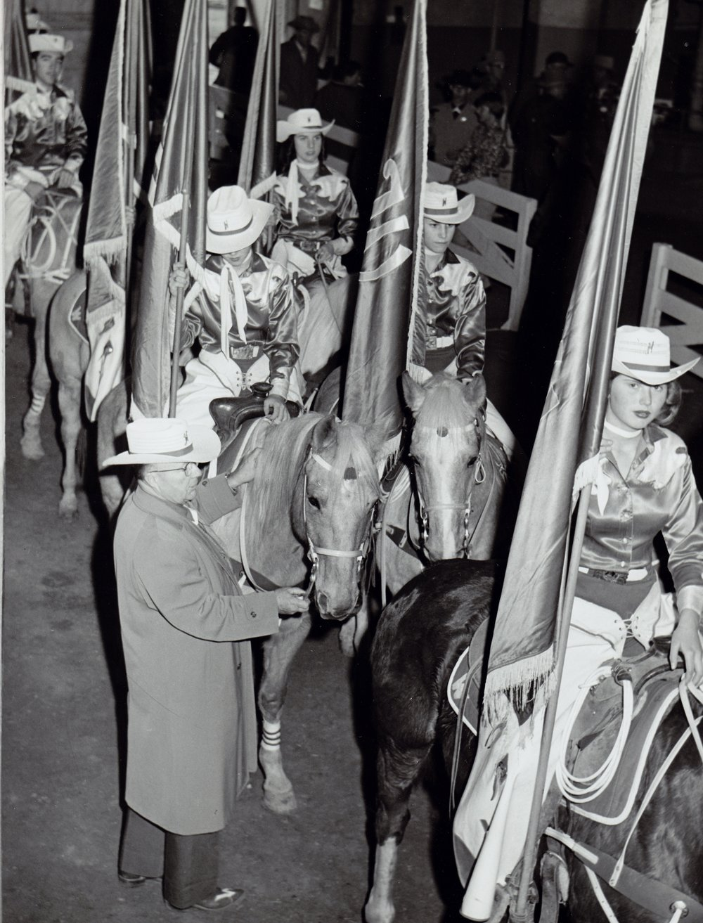 Westernaires founder and Director, Elmer E. Wyland, stands with the lined-up Grand Entry riders in the paddock of the 1961 National Western Stock Show. Jody Williford is on the far right.