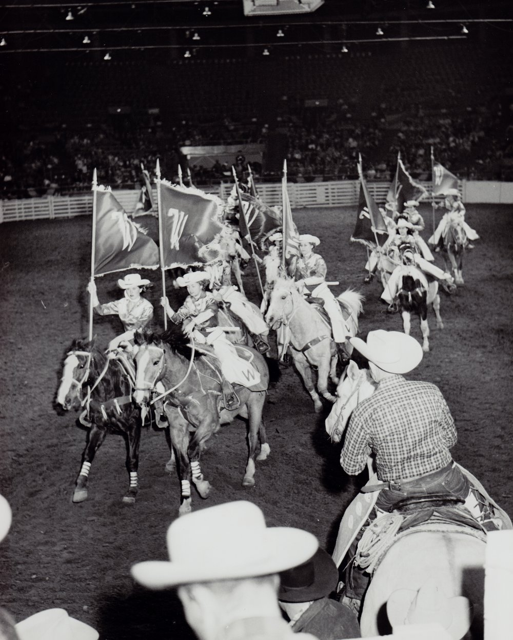 Jody Williford and Peggy Warren lead the team out of the arena, 1961.