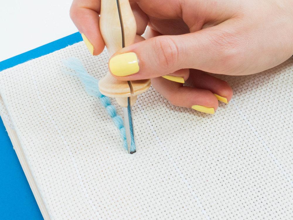 Mit der Punch Needle wird von der Rückseite aus gearbeitet. In regelmäßigen Abständen sticht man mit der Nadel in den Stoff.