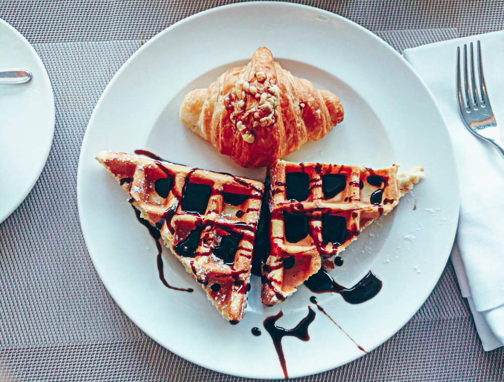 The Atana Hotel Dubai Garden Restaurant with a plate of croissants and waffles drizzled in chocolate sauce.
