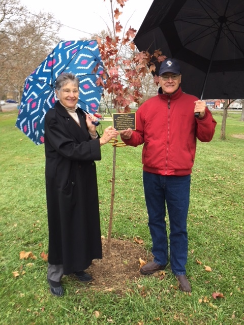 Mary anne bacas presents the plaque to jim gross as they stand in front of the tree