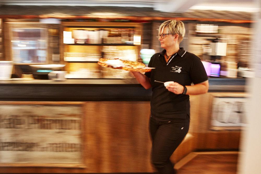 Servitør på vei ut i kafeen