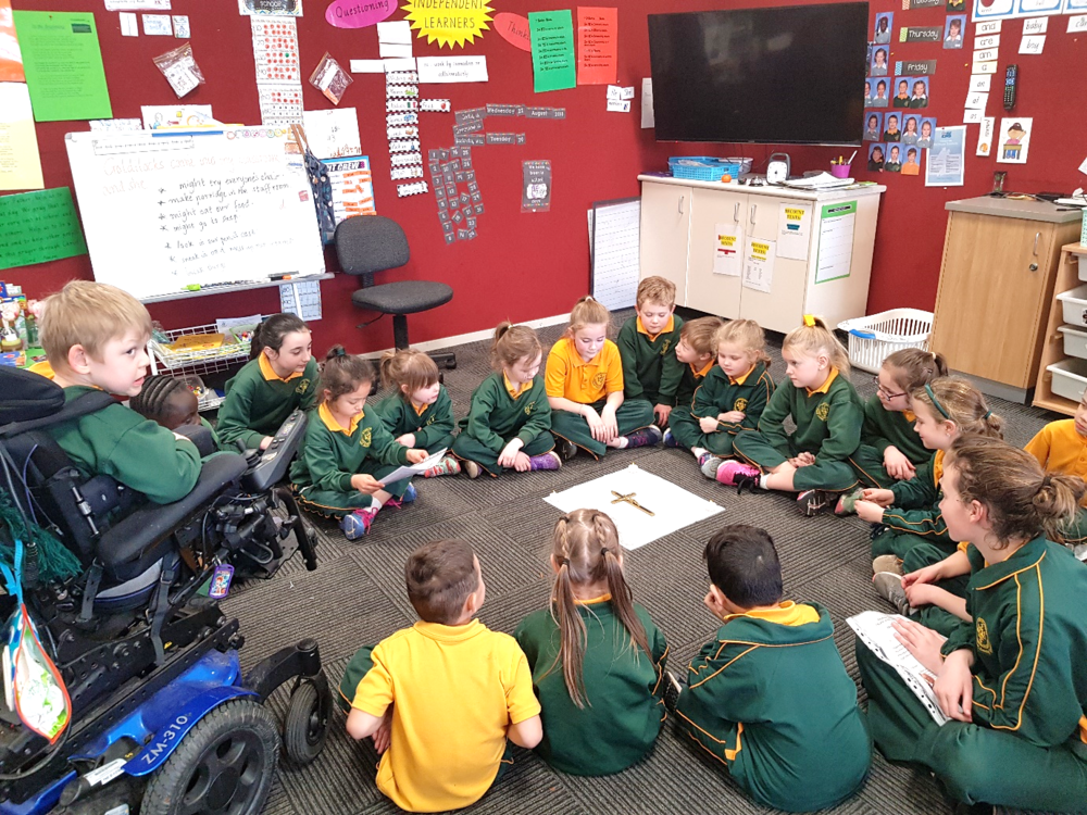 """The """"Mini Oblates"""" of St Kieran's Primary School, Moe lead a class in prayer with the cross of Fr Dunlea."""