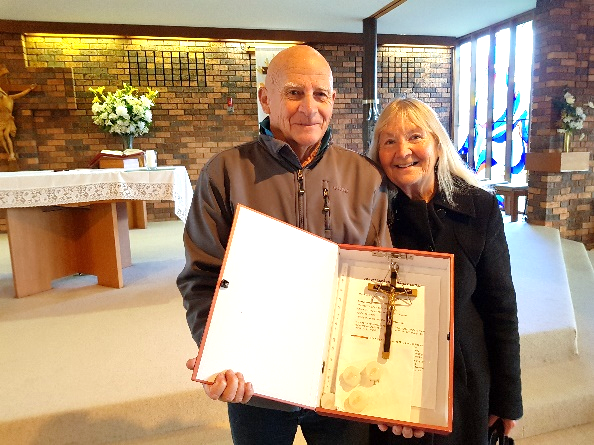 Cliff and Wilhelmina receive the cross of Fr Dunlea at the celebration of the Eucharist at St Mary's, Newborough.