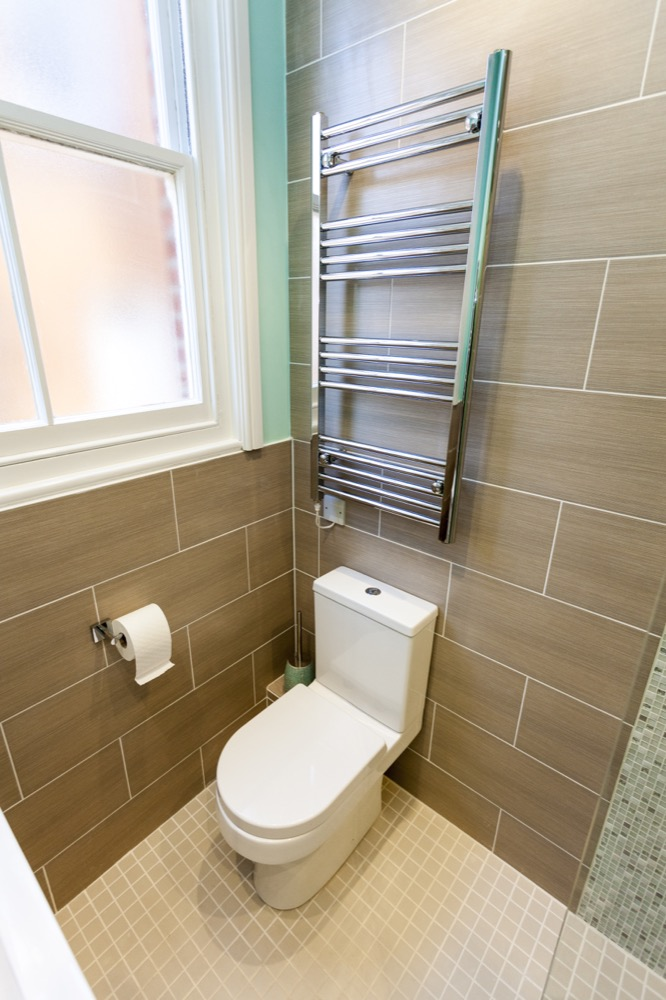 Chrome towel rail with low-level WC. Emperor Bathrooms.
