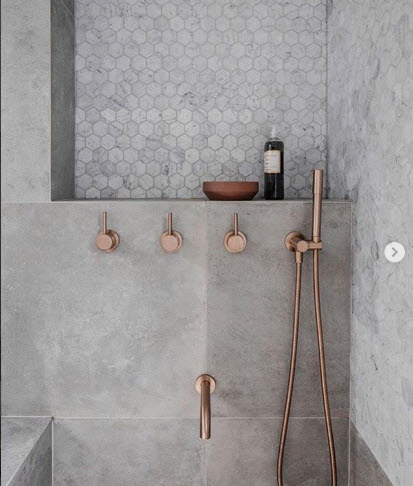 Alexander and Co showcases the glory of Rose Gold Plumbing Fixtures standing out against the beautiful cement and Tile Shower Walls.
