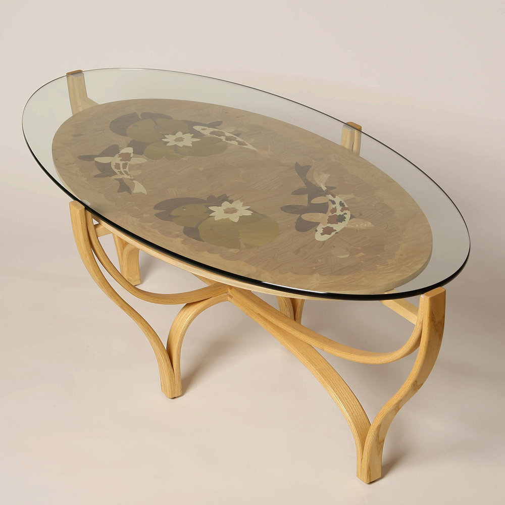 the Koi Pond Coffee Table   The base of    Koi Pond Coffee Table    is designed to resemble a pond.  It is a series of bent laminations, made of ash, and joined to form the base.