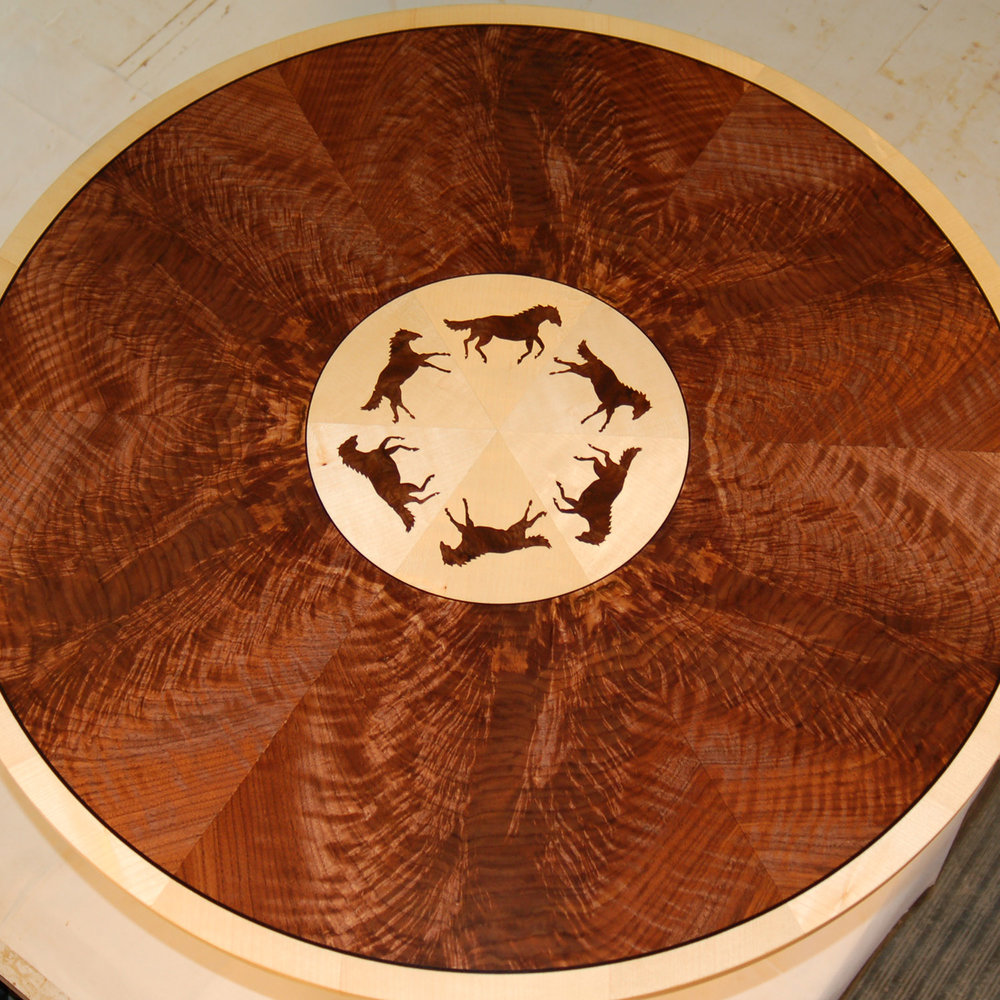 Holly and Crotch Walnut   The center of this tabletop is a 6-sector pie-match of holly, surrounded by a 12-sector pie-match of crotch walnut.  A ring of 6 inlaid horses decorates the center.