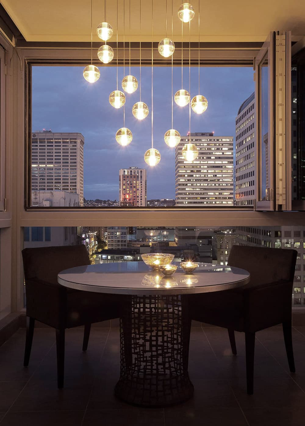 Inside | OUT - In the midst of the city, the outdoor dining room is a dramatic evening spot. The pendant glass lights mimic the evening city lights. The steel table base and silver leaf top capture the city textures.