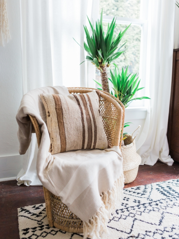 Bohemian bedroom decor with neutral kilim pillows and rattan chair with Foraged Home