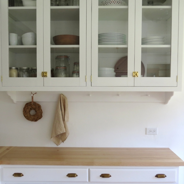 All white craftsman bungalow kitchen inspiration with white cabinets, butcher block counters and vintage aesthetic at Foragedhome.com