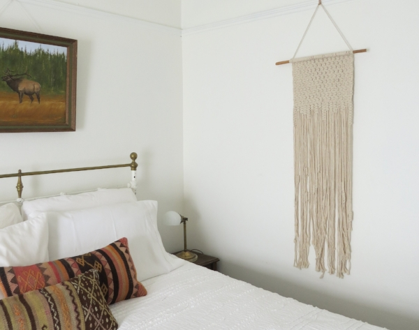 Simple and clean bedroom design with boho style kilim pillows and macrame from Foraged Home