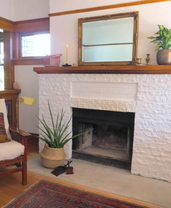 White fireplace and natural wood color mantel in Bungalow Craftsman style home from Foragedhome.com