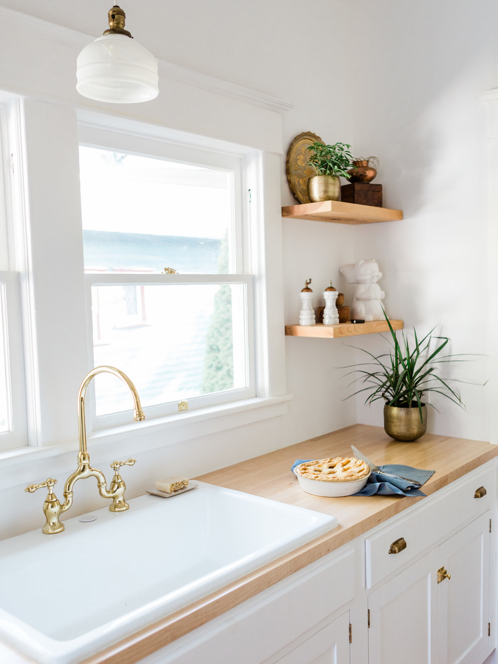 All white kitchen with butcher block counter tops and open shelves from Foraged Home