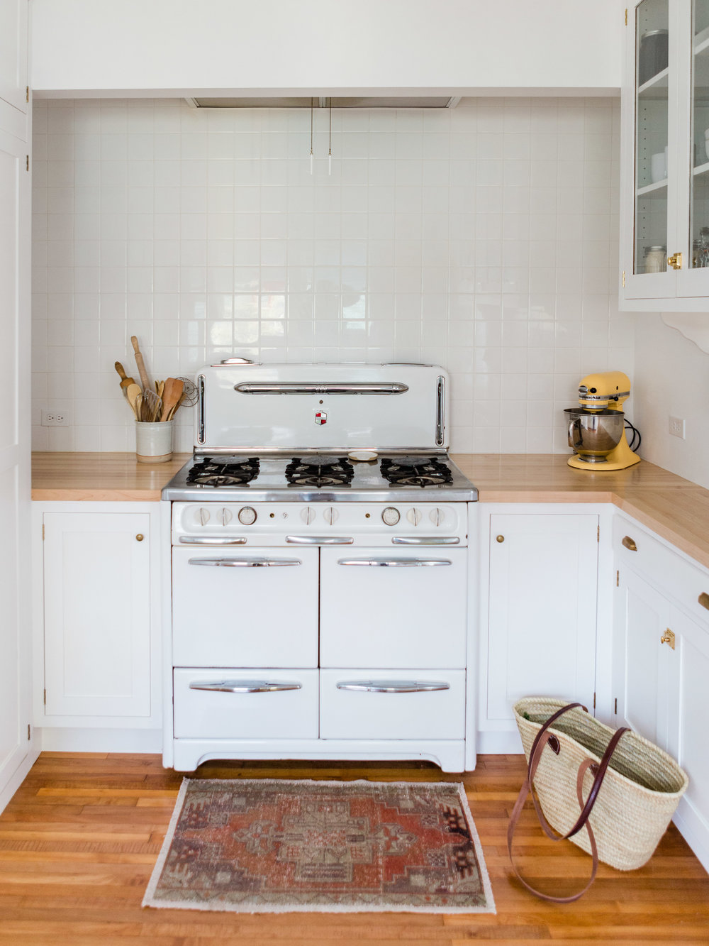 All white kitchen with vintage style stove and Turkish kilim rug from Foragedhome.com