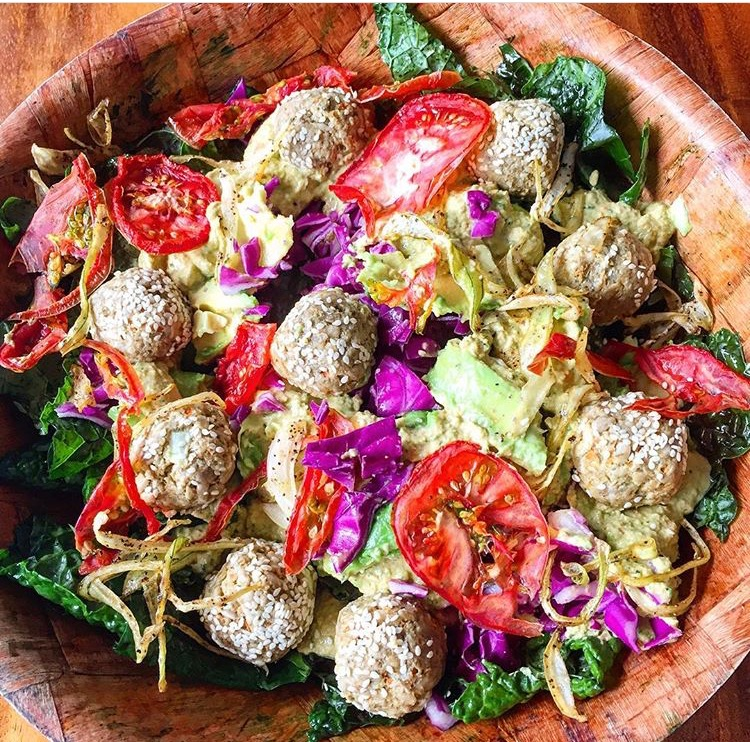 Pictured is the falafel on massaged kale (with avocado oil & sea salt), dehydrated tomato & onions, chopped red cabbage, avocados, and drizzles with tahini and fresh lemon juice.