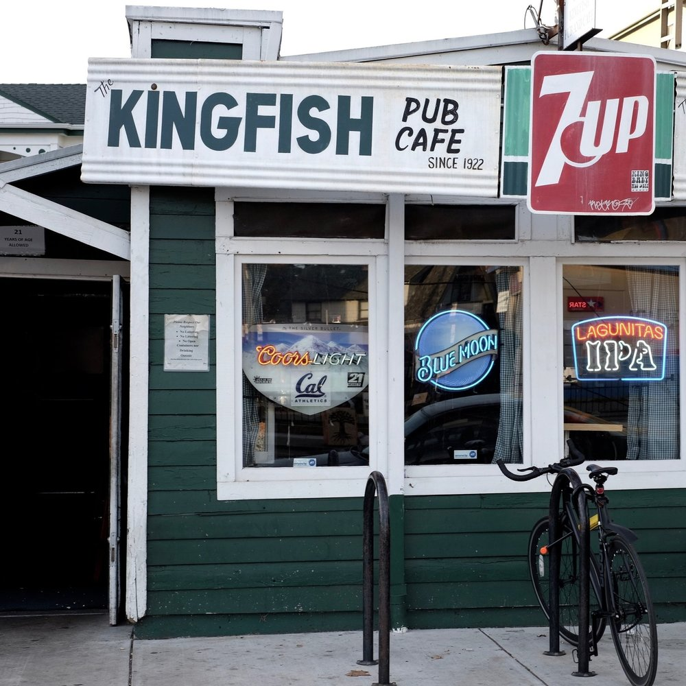 Kingfish:  Free popcorn, happy hour, dive bar. Its a classic loved by locals and includes covered back patio (and shuffle board!).
