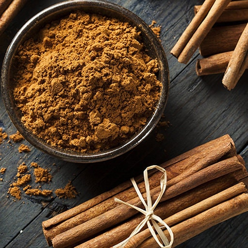 ground cinnamon and cinnamon sticks in a bowl