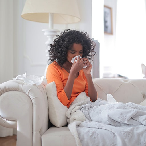 woman covered with blanket blowing nose hay fever