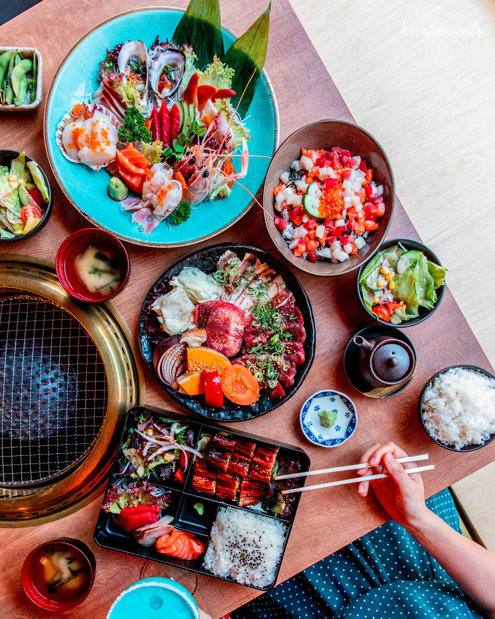 Hero Flatlay at Touka Restaurant, showcases bright and beautiful dishes in an elegant BBQ setting on clean Japanese wood.