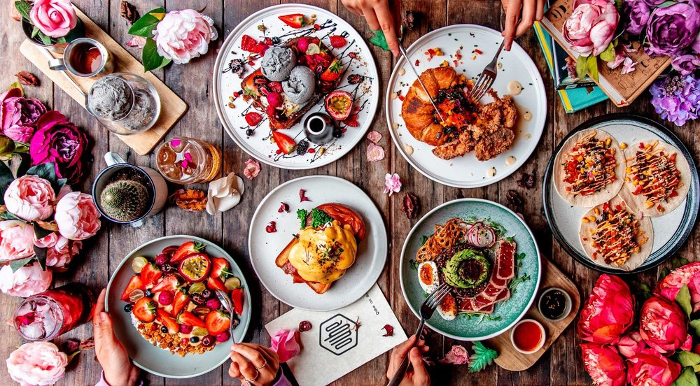 Hero Flatlay at Qube Cafe illustrates a quirky, creative persona that matches its dishes; complimented by floral props that enhance rather than distract.