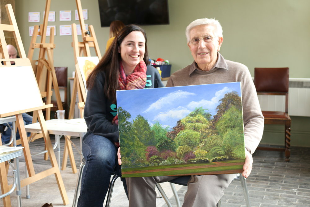 Terry with his daughter Sheryl and his painting of the Clifford House gardens.
