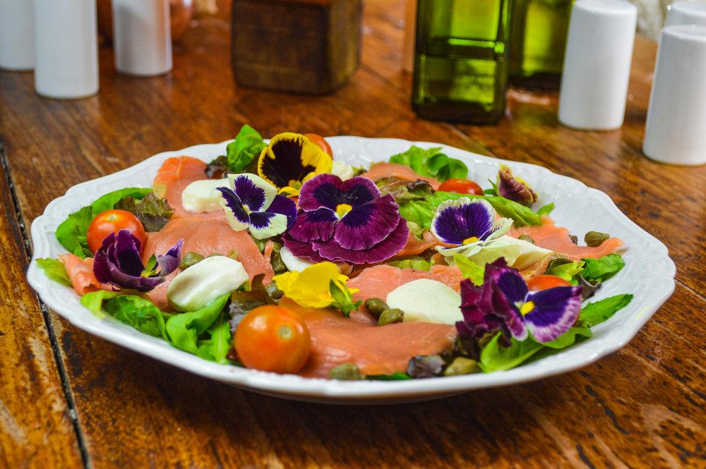 Salada de salmão com amor-perfeito, tomates cereja, alcaparras, folhas verdes e queijo de búfala da @fornellonepízzaria
