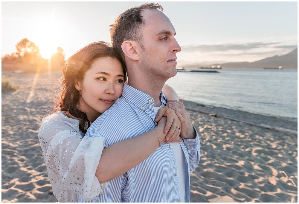 engaged Couple embracing at Jericho beach in Vancouver during engagement photography session with wedding photographer