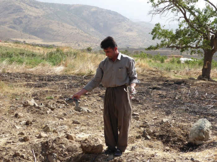 Villager from Barbzin village showing CPT remnants  of an Iranian bomb that burnt his field. June, 2016.