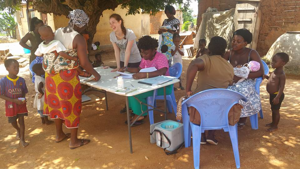 Nutrition Volunteer from the U.K., Bruna, checks the weekly measurements of children in the Point Hope Community Nutrition Outreach program, with the help of Point Hope Staff and Ghana Community Health Nurse.