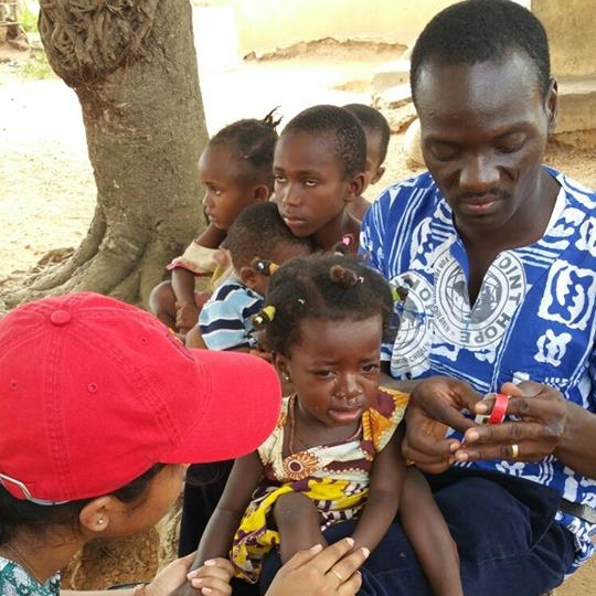 Adam Sandow still finds time to work in his field of Nutrition. Here he is working with a volunteer to measure a child for clinical malnourishment during the Point Hope Community Nutrition Outreach project done periodically in villages throughout the Central Region in Ghana.