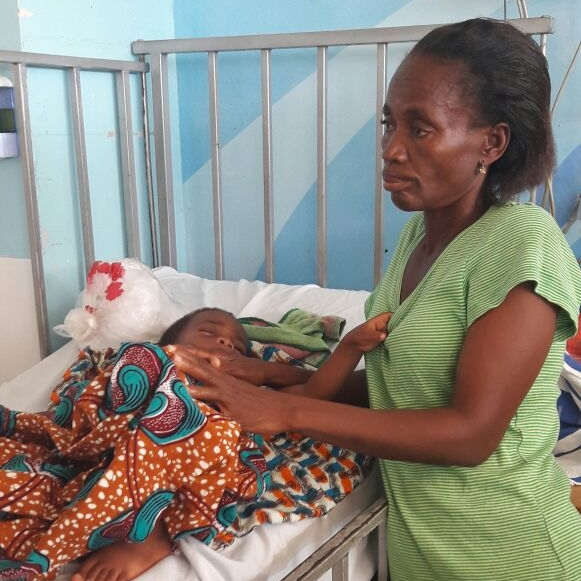 Mama Agnes stands by Oliver at Korle Bu Hospital in the Children's Ward during his early days of chemotherapy.