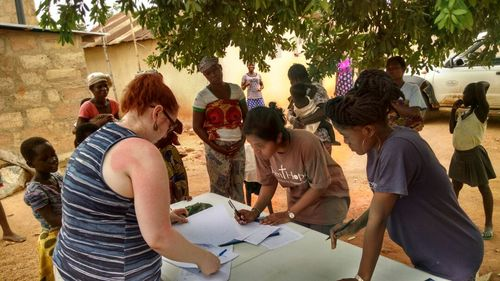 Nicole, from Washington State, Tasneem, from Kentucky, and Stella from Ghana, all working together to process children at the Nutrition Outreach project.